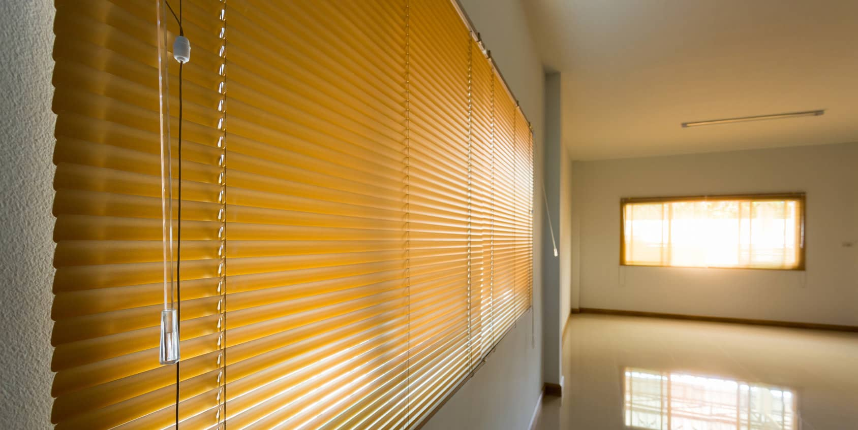 long slider blinds covering window of empty room